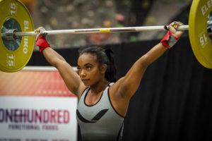Kvinnlig tyngdlyftare lyfter skivstång under tävling.